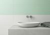 Biała umywalka nablatowa w miętowej łazience