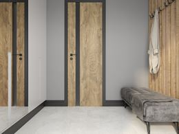 Przedpokój wykończony drewnem i jasnym betonem