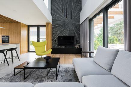 Salon z wysokim sufitem i czarną ścianą