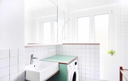 Biała łazienka z oknem i pralką