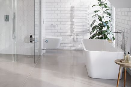 Biała łazienka z cegiełką i wanną wolnostojącą