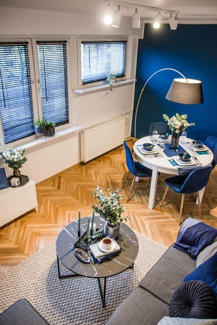 Strefa jadalna w stylowym salonie z granatową ścianą