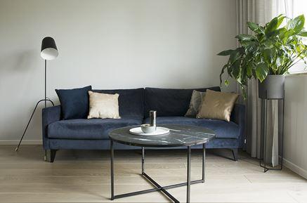 Granatowa kanapa i marmurowy stolik