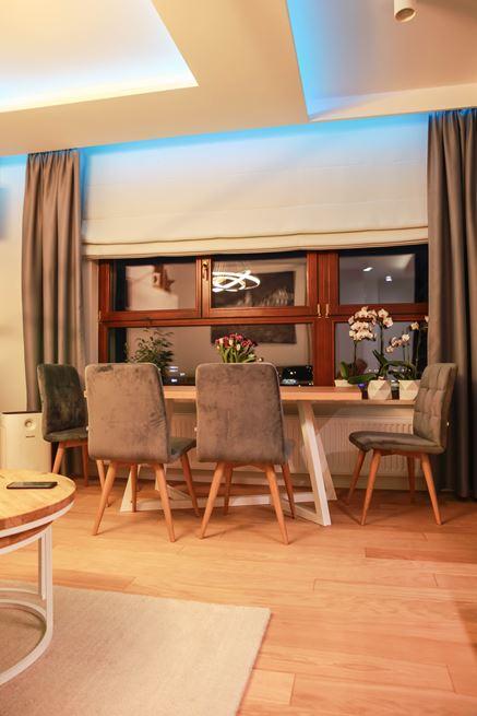 Strefa jadalna pod oknem w nowoczesnym salonie