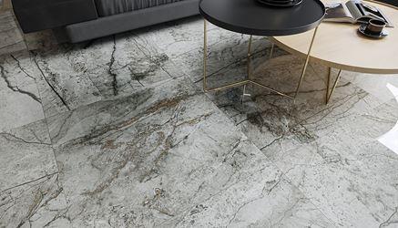 Podłoga w salonie wykończona polerowaną płytką w szarej kolorystyce