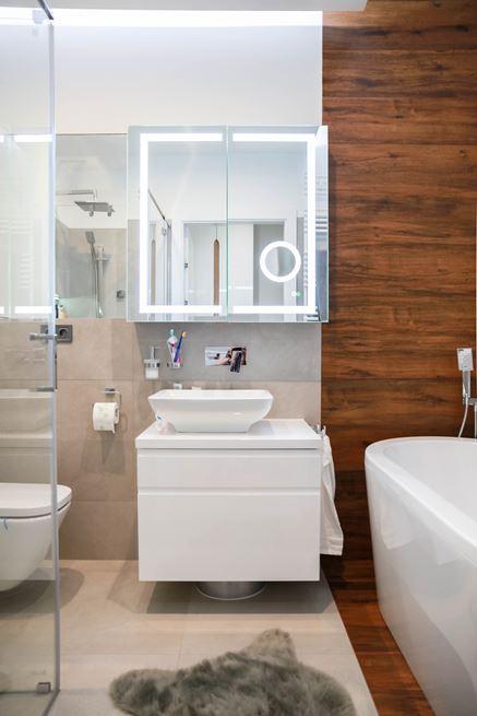 Biel i drewno w małej łazience z wanną