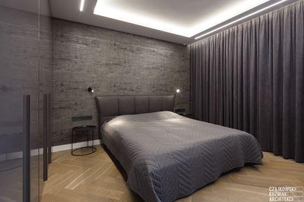 Minimalistyczna sypialnia z szarą ścianą