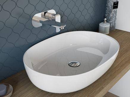 Owalna umywalka nablatowa i niebieska mozaika w tle