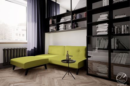 Żółta kanapa na tle czarnej zabudowy