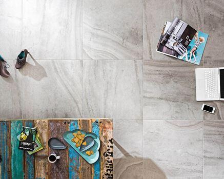 Podłoga w salonie wykończona płytkami z rysunkiem kamienia