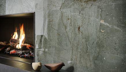 Ściana kominkowa wykończona polerowaną płytką imitująca kamień
