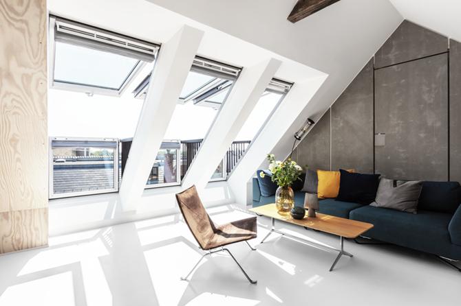 Strefa wypoczynkowa z betonową ścianą i dużymi oknami