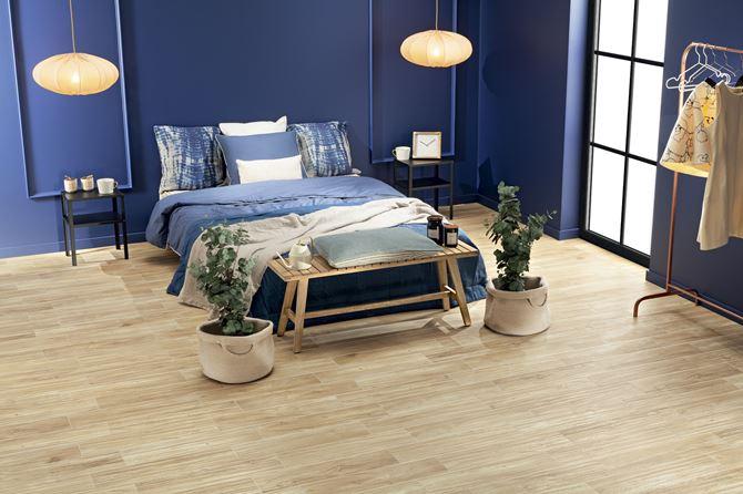 Granatowa sypialnia z podłogą w beżowym drewnie