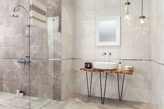 Kremowa łazienka wykończona kamiennymi, połyskliwymi płytkami