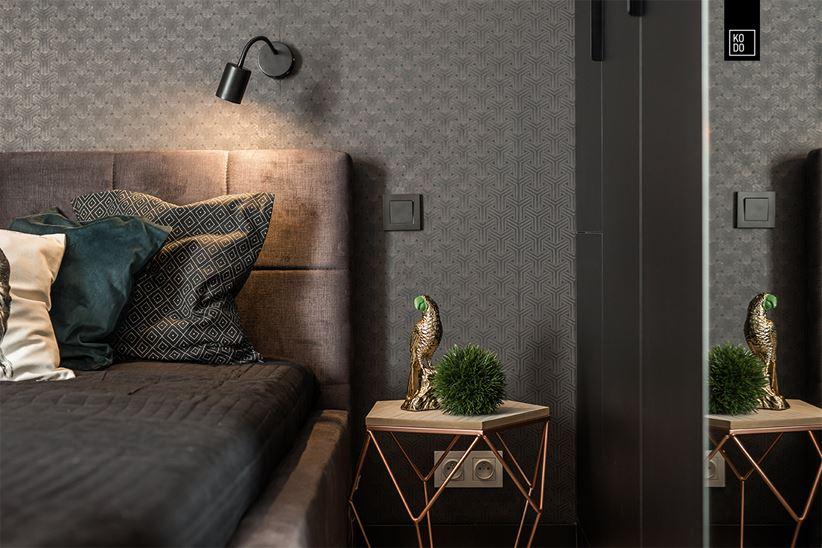 Detale ciemnej sypialni - ażurowy stolik nocny