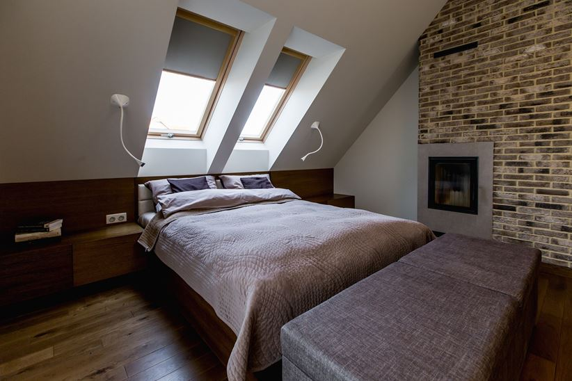 Sypialnia na poddaszu z szarą cegłą i kominkiem