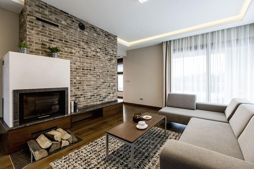 Ceglana ściana z kominkiem w nowoczesnym salonie
